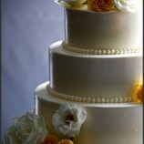 Simple dot wedding cake with yellow flowers